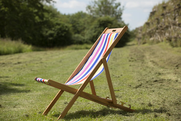 Colorful stripped deck chair open on the grass