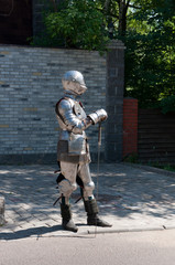 knight in the ancient metal armor near the stone wall