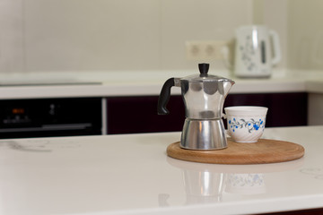 Coffee percolator and cup on a kitchen counter