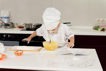 Excited young chef leaning over mixing bowl