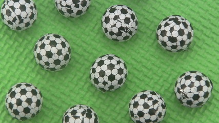 Candy footballs rotating on a green background.