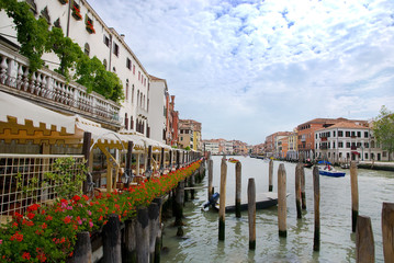 Venice channel and seafront with red flowers, Italy