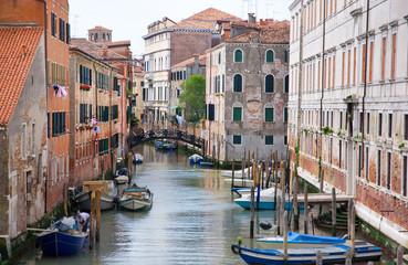 Venice canal with gondolas, boats and small bridge. Italy