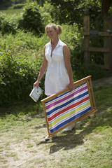 Woman walking carrying a deck chair and a book