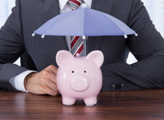 Businessman Sheltering Piggybank With Umbrella At Desk