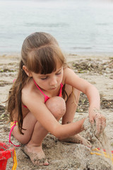 Girl playing with sand on the sea shore