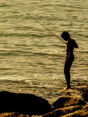 Niño pescando en la costa