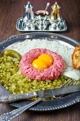 Fresh steak tartar with pickled cucumber and onion