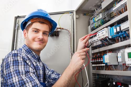 Technician Examining Fusebox With Multimeter Probe - 66234695