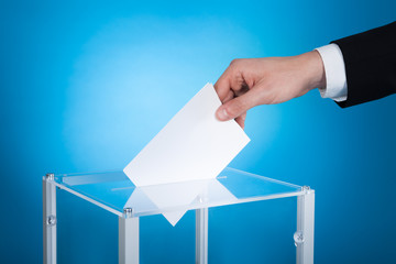 Businessman Putting Paper In Election Box