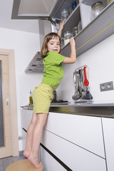 Little girl on a chair to reach higher to get chocolates