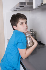 young boy taking candy from a high kitchen cabinet