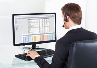 Businessman In Headset Using Computer At Desk