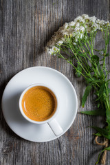 Espresso coffee and a small bouquet of flowers