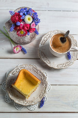 Cheesecake, cup of coffee and spring flowers