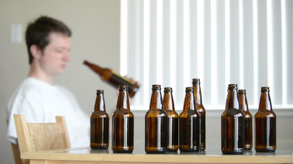 Drunk man looks for more beer in empty bottle