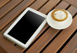 Cappuccino coffee white cup with tablet on wooden table