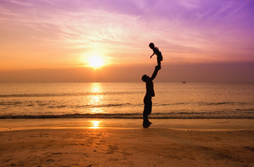 father and son on sunset beach,silhouette