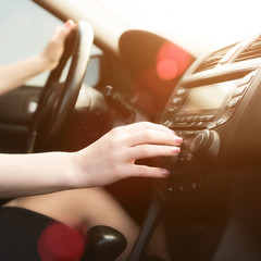 Woman in a car use audio system