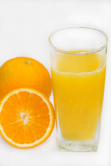 Glass of freshly pressed orange juice with sliced orange  on woo