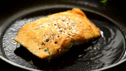 Fresh salmon steak cooking in a frying pan close up