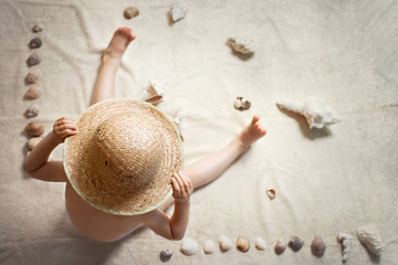 Little boy with straw hat, sitting on the ground, sea shells aro