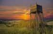 Hunters lookout tower on the field at sunset.