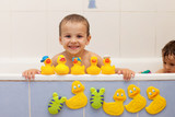 Fototapety Adorable little boys in bathtub with his rubber duckies