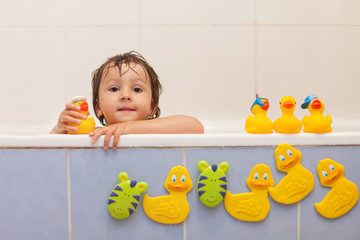 Adorable little boy in bathtub with his rubber duckies