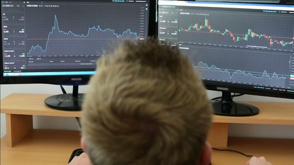 Man works on the financial market (exchange) on computer