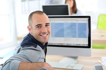 Portrait of student in front of desktop computer