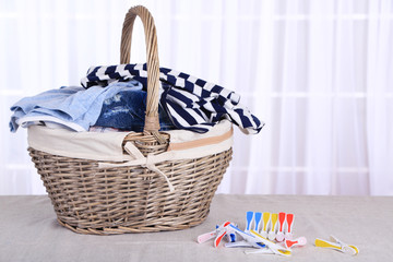 Colorful clothes in basket and pins