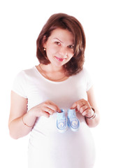 Portrait of pregnant woman with baby shoes