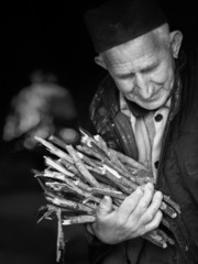 Elderly, poor man carrying firewood