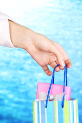 Hand holds package with New Year gift on blue background