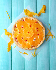 Homemade orange tart on color wooden background