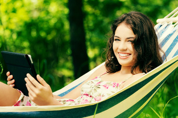 Woman lying in a hammock in garden with E-Book.
