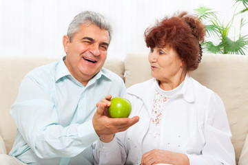 Laughing senior couple hold green apple