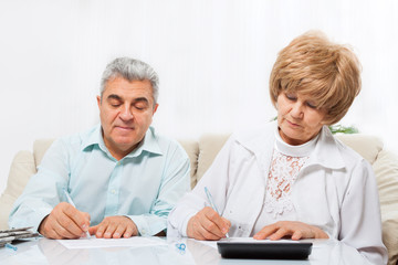 senior couple sign up document sitting sofa