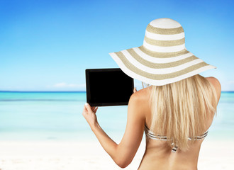 Blond girl with tablet on tropical beach