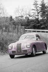 Violet classic car on black and white background