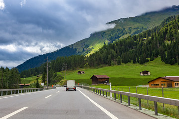 Highway along green fields and mountains in Switzerland.