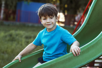 Little caucasian boy smiling on slide