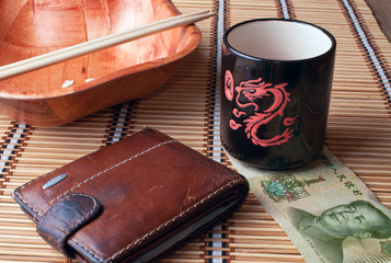 cup, plates, chopsticks, purse and bill on a bamboo napkin