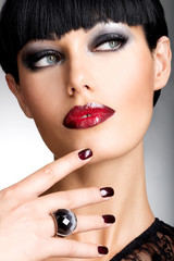 Face of a woman with beautiful dark nails and sexy red lips