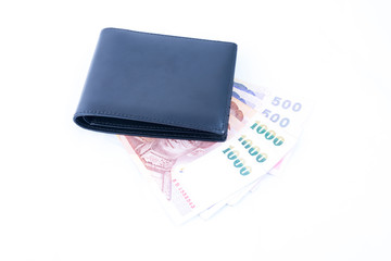 Money under leather wallet. Isolated on a white background.
