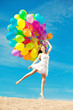Beautiful young stylish woman with ainbow balloons in hands agai