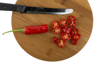 Chopped red chili peppers on wooden plate