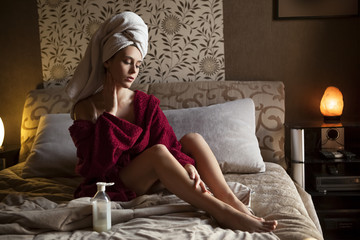 Beautiful young woman in bathrobe applying moisturizer cream