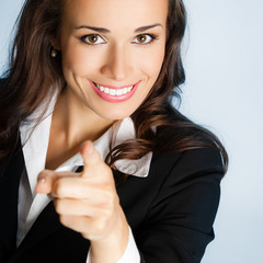 Business woman pointing finger at viewer, over blue